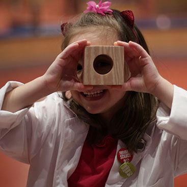 A young girl looks through a hole in a wood block.